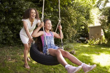 タイヤ ガーデンでスイングに押す娘を母します。 写真素材