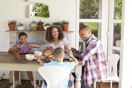 Familia al aire libre en casa comiendo la comida junto