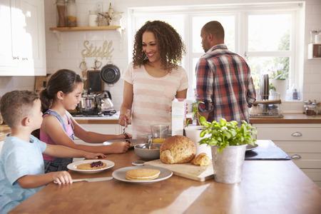 niños desayunando: Familia en el país que come el desayuno en cocina junto Foto de archivo
