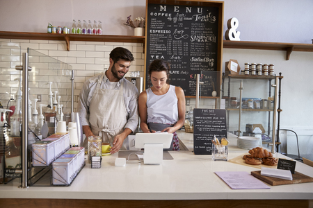 front view: Couple working together at the till in a coffee shop
