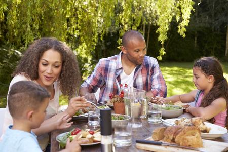 Familia en casa comiendo comida al aire libre en el jardín juntos