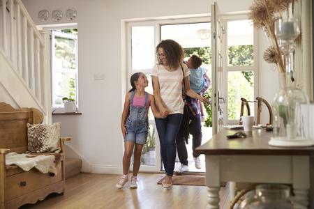 Familie in de hal naar huis terugkeren Together Stockfoto