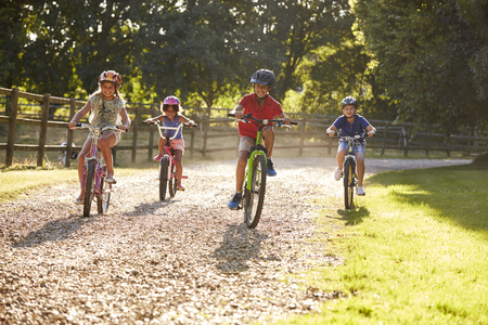 negras africanas: Four Children On Cycle Ride In Countryside Together Foto de archivo