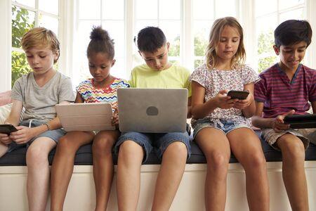 子供たちのグループは窓側の席に座るし、技術を使用して 写真素材