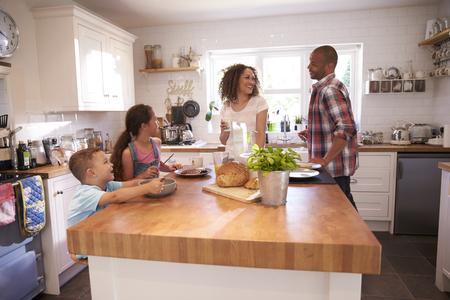 Família em casa que comem o pequeno almoço na cozinha junto
