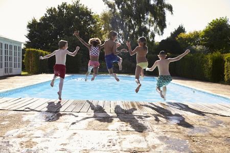 niños negros: Vista posterior de los niños Salto En Piscina al aire libre