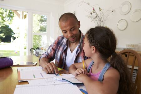 black male: Father Helping Daughter With Homework At Table