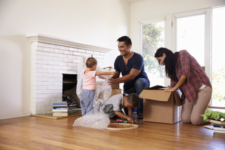 Family Unpacking Boxes In New Home On Moving Day Imagens - 71214426