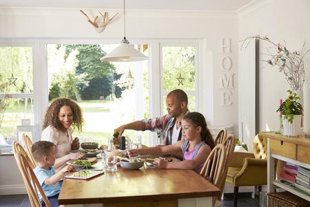Familia en el país que come la comida en cocina junto Foto de archivo - 71214436