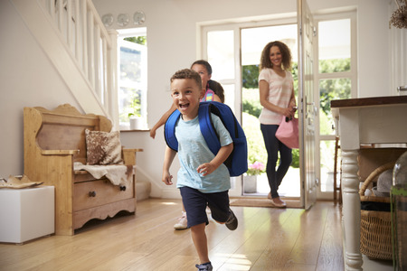 Les enfants excités retournent chez eux de l'école avec la mère