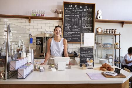 カメラをコーヒー ショップのカウンターの後ろの女性 写真素材