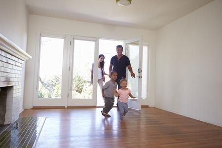 Aufgeregte Familie Erkunden Sie Neues Zuhause am Tag der Bewegung