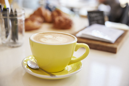 cappuccino cup: Large cappuccino coffee in yellow cup and saucer on counter Stock Photo
