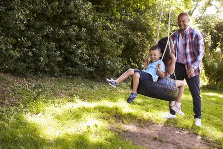 정원에서 타이어 스윙에 아이들을 밀고 아버지 스톡 콘텐츠
