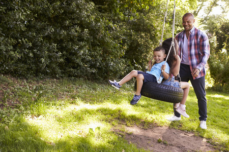 Father Pushing Children On Tire Swing In Garden Banque d'images