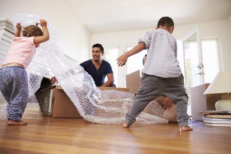 Familie uitpakken van dozen in het nieuwe huis On Moving Day Stockfoto