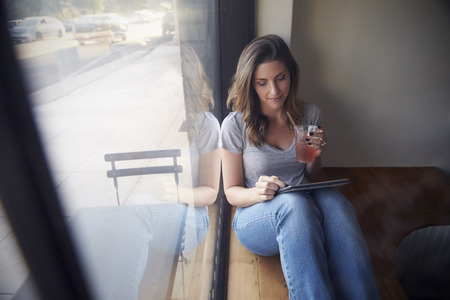 t bar: Young woman sits beside window in cafe using tablet computer