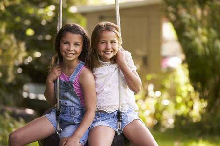 정원에서 스윙 타이어에 재생 두 여자의 초상화 스톡 콘텐츠