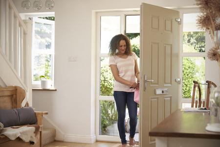 Femme rentrant à la maison et ouvrant la porte avant