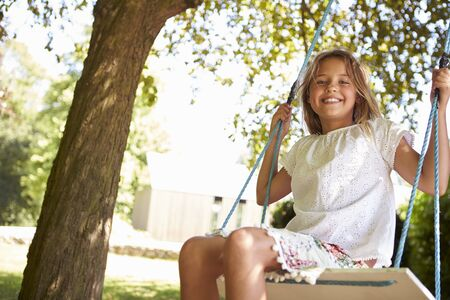 looking at camera: Portrait Of Young Girl Playing On Tree Swing
