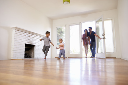 Excited Family Explore New Home On Moving Day Stockfoto
