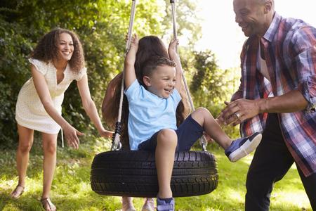 정원에서 타이어 스윙에 아이들을 밀고 부모