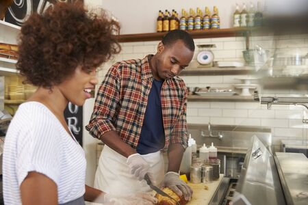 man looking down: Black couple prepare food behind counter at a sandwich bar