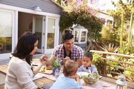 familia orando: Familia que dice la tolerancia antes de la comida al aire libre en jardín Foto de archivo