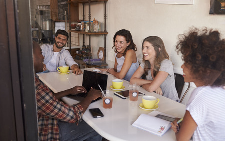 seen: Young adult friends hanging out in cafe, seen through window Stock Photo