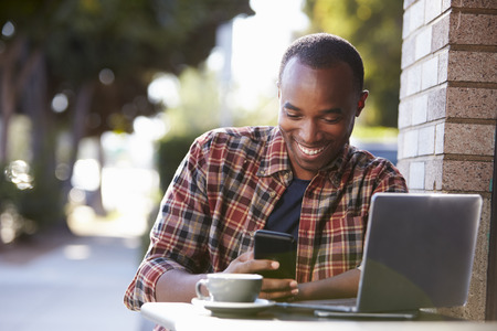 Young black man outside a cafe looking at his smartphone