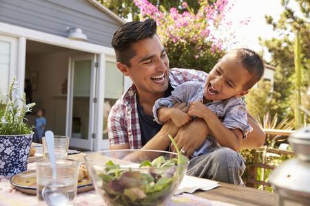 Vater und Sohn essen im Freien Mahlzeit im Garten zusammen