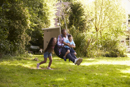 Daughter Pushing Father And Son On Tire Swing In Garden Stock Photo