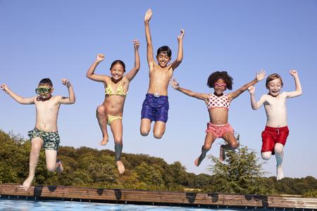 屋外スイミング プールに飛び込む子供たちのグループ
