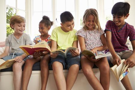 Gruppo di bambini multiculturali che leggono sul sedile di finestra Archivio Fotografico