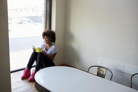 窓からカフェで女性の写真を撮る写真家