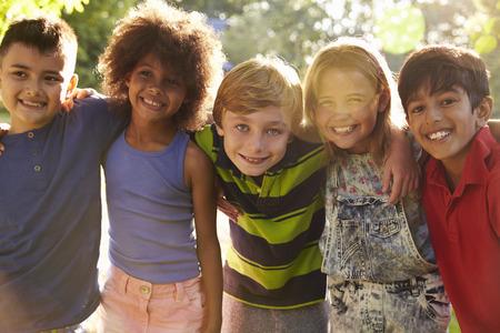 Retrato de cinco niños que se divierten juntos al aire libre Foto de archivo