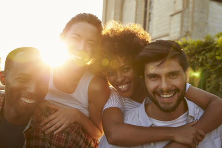 arms around: Two happy young adult couples piggybacking the street