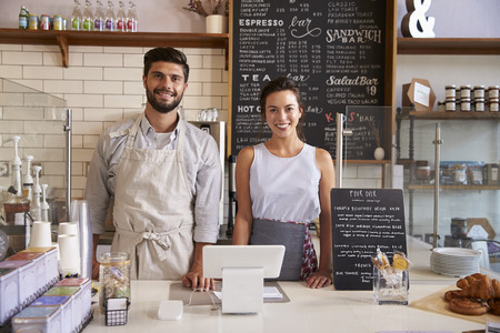Couple ready to serve behind the counter of a coffee shop