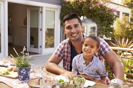 Padre e hijo comiendo comida al aire libre en el jardín juntos Foto de archivo - 71214903