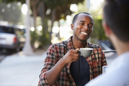 black guy: Two adult male friends sit talking over coffee outside cafe