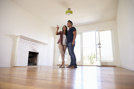 pareja en casa: Excited Couple Explore New Home On Moving Day