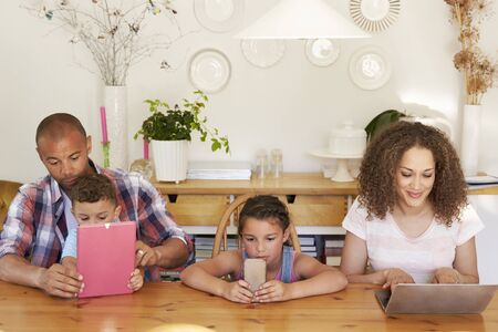 laptop: Family Sitting Around Table At Home Using Technology