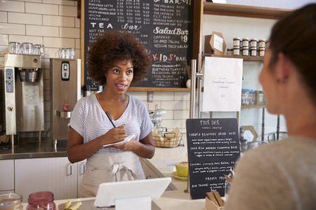 business service: Waitress writing customer?s order at counter of coffee shop