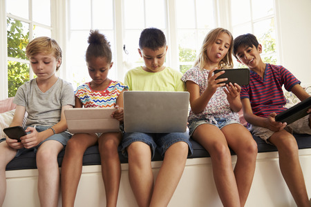 Gruppo di bambini Sedersi al posto finestra e utilizzare la tecnologia