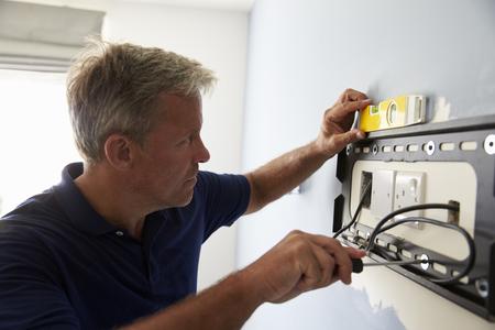 벽에 플랫 스크린 TV를위한 남자 피팅 브래킷 스톡 콘텐츠