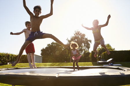 trampoline: Group Of Children Having Fun Jumping On Outdoor Trampoline