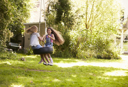 Twee Meisjes spelen samen op Schommeling van de band in Tuin