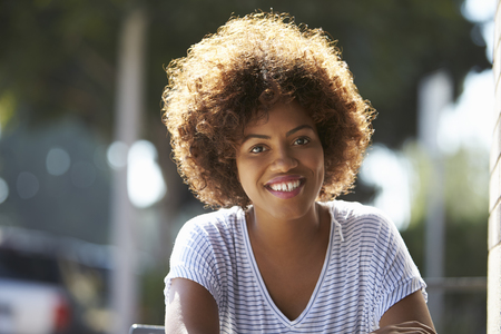 Portrait of happy young black woman sitting outdoors Imagens