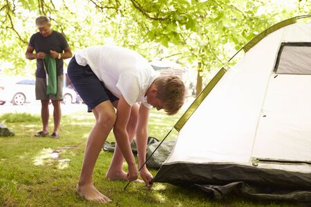 pitching: Father And Teenage Son Putting Up Tent On Camping Trip