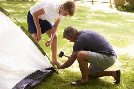 campsite: Father And Teenage Son Putting Up Tent On Camping Trip